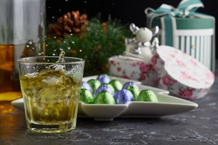 A glass of whiskey on the background of a Christmas wreath with cones, Christmas toys, gifts and a plate of sweets. 版權商用圖片