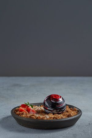 Exquisite dessert in the form of a chocolate ball with caramelized bread crumbs, decorated with strawberries and mint leaf on a plate. Copy space.