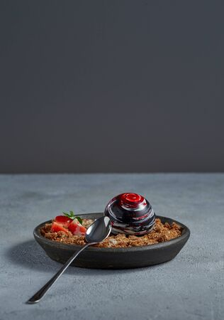 Exquisite dessert in the form of a chocolate ball with caramelized bread crumbs, decorated with strawberries and mint leaf on a plate with a spoon. Free space for your text.