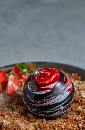Close-up of an exquisite dessert of a chocolate ball lying on caramelized dark bread with almond crumbs, garnished with strawberries and mint, with a creamy sauce on a clay plate. Vertical.
