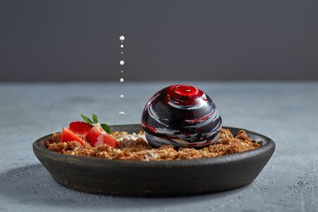 Close-up of a gourmet dessert with a colored chocolate ball and caramelized bread crumbs with almonds, strawberries, mint leaves and drops of creamy sauce hovering over it. Free space for your text.