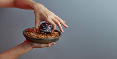 Close-up of an exquisite dessert of a planet-like colored chocolate ball in the hands of a boy, with caramelized dark bread with almond crumbs, garnished with strawberries and mint. Copy space.
