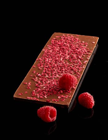 Chocolate bar with dried homemade raspberries and three fresh raspberries on top, isolated on a black background with reflections. Banco de Imagens