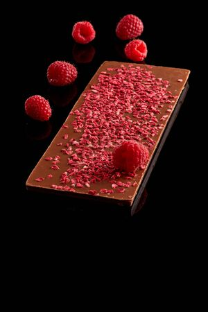 Whole bar of chocolate with stabilized raspberries and fresh berries isolated on a black surface.