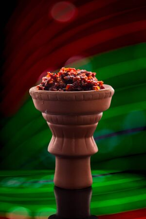 Shisha in a clay bowl stands against a beautiful red-green bokeh on a glossy surface with reflections. Traditions of hookah Smoking.