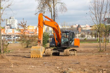 Industrial excavator stands on a cleared construction site.