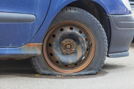 Old rusty abandoned car with a flat tire. Stockfoto
