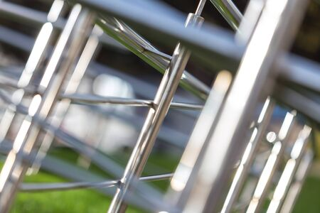 Abstract chrome metal background of bent pipes of different diameters with blur effect. Selective focus. Stockfoto