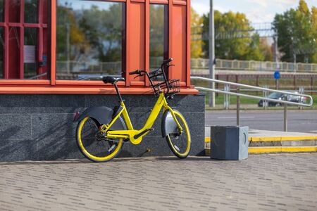 Unoccupied bike sharing in a public place. Sharing a yellow bike on the street. Change of transport.