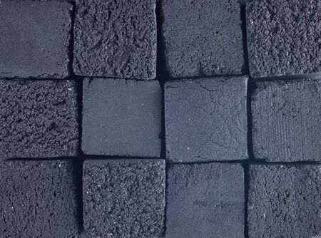 Coconut charcoal pressed in the form of cubes. Top view. Texture and background.