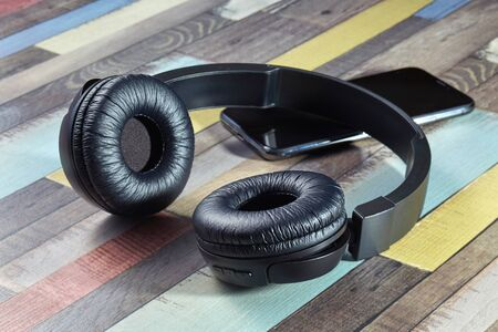 Wireless headphones. Modern powerful black wireless headphones and smartphone on a wooden surface of bright coloring.