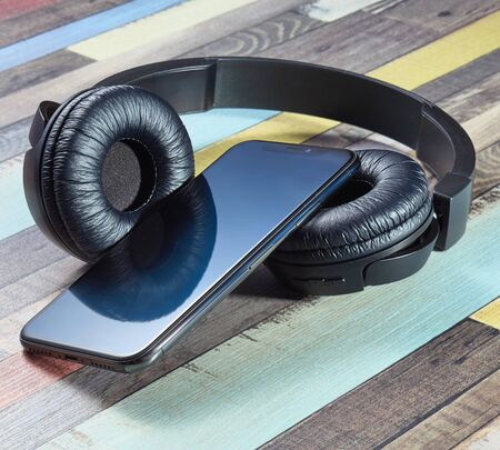 Wireless headphones and smartphone. Modern powerful black wireless headphones on a wooden surface of bright coloring. 스톡 콘텐츠