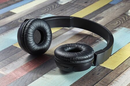 Wireless headphones. Modern powerful black wireless headphones on a wooden surface of bright coloring.