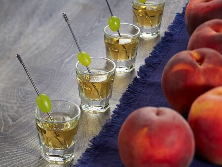 Shot of four servings of Grappa with grapes on skewers and ripe peaches on a blue napkin on the wooden surface of the table. Horizontal image. Reklamní fotografie