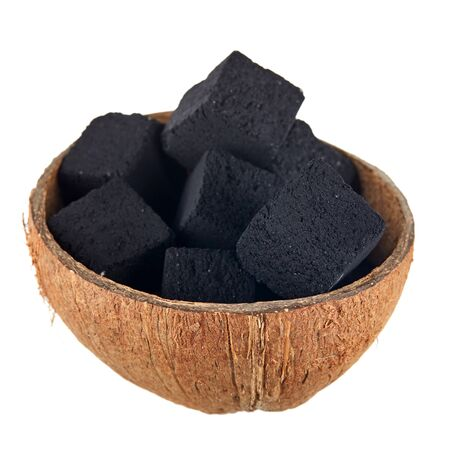 Coconut coal in half a coconut shell on a white background. Coconut charcoal cubes for hookah close-up.