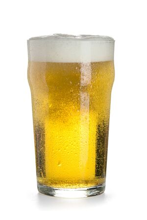 Pint of light cold beer in a glass with a thick cap of foam, bubbles and drops of condensate, isolated on a white background.