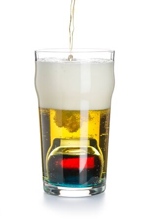 Depth charge cocktail of beer, Blue Curacao liqueur, grenadine and vodka, prepared by mixing a submerged inverted Cup at the bottom of a beer glass isolated on white. The process of filling a glass. Banco de Imagens