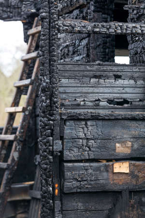 Charred boards of the interior walls of a room that burned in a fire with a staircase in the background.