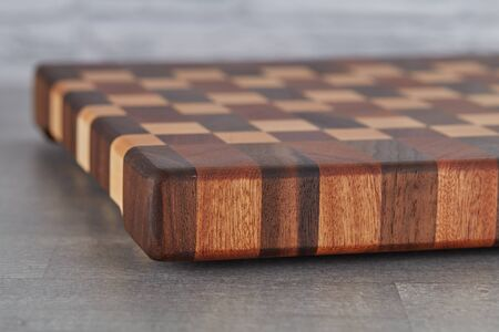 Beautiful cutting Board made of different types of wood, lying on the table.