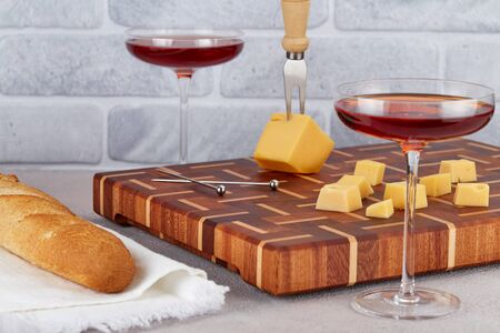 Two elegant glasses of red wine on a thin stem, sliced cheese and bread on a cutting Board with a beautiful pattern, standing on the kitchen table. Mediterranean snacks and wines.