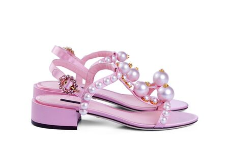 Pair of women's open satin pink shoes with large pearls and a brooch clasp, isolated on a white background with a light shadow.