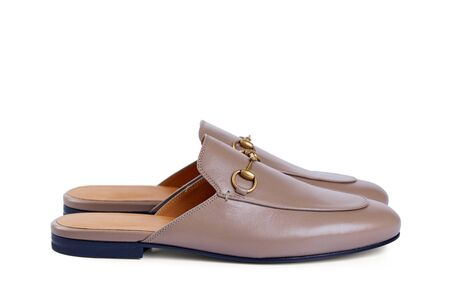 Mens lightweight home shoes in thin beige leather with elegant metal buckle without backrests insulated on white background with shadow. Side view.