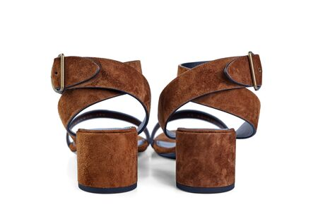 Pair of womens open sandals in high heel of brown suede, isolated on a white background by a light shadow. Rear view.