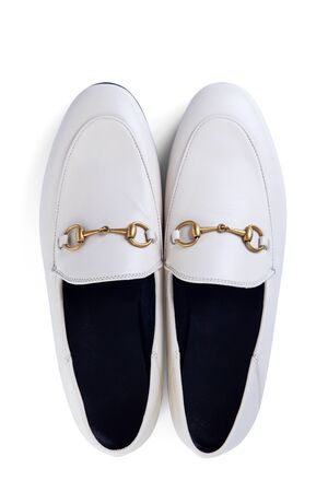 Mens lightweight shoes in fine white leather with an elegant metal buckle insulated against a white background with shadow. Top view.