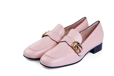 Pair of Gucci women's shoes made of thin soft pink leather with a low heel, isolated on a white background with a light shadow.