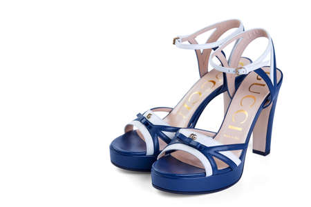 Pair of womens open GUCCI sandals made of thin white and blue leather with high heel, isolated on a white background by a light shadow. Top view at an angle. Belarus, Minsk, 22.04.2020. Editorial