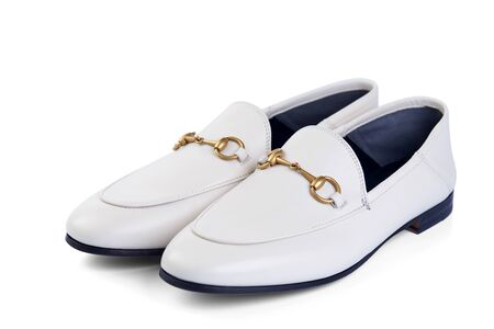 Mens lightweight shoes in fine white leather with an elegant metal buckle insulated against a white background with shadow. Top view at an angle.