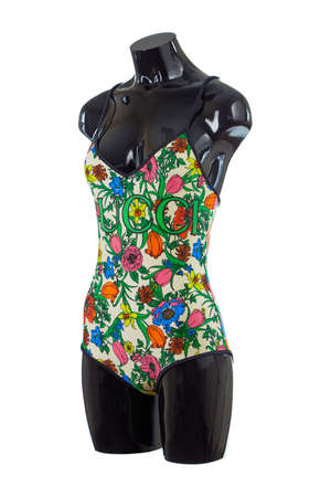 Women's closed swimsuit with a bright floral print Gucci logo on the chest, isolated on a white background.