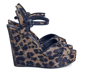 Pair of women's open sandals on a platform made of leopard-coloured fabric with leather trim, isolated on a white background with a light shadow. Imagens