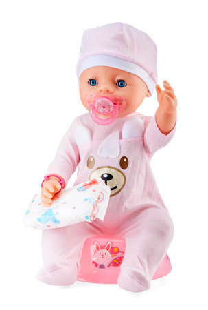 Plastic plastic baby doll with a pacifier in its mouth sits in childrens clothes on a baby pot with a diaper in hand, isolated on a white background.