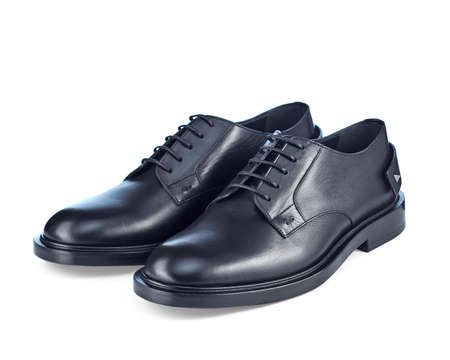 Beautiful pair of classic mens black leather shoes on lace, complemented by imitation spurs on the heel, isolated on a white background with a shadow.