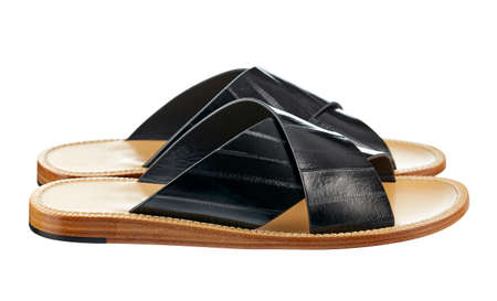 Mens summer sandals made of black crocodile leather with a low sole, isolated on a white background. Side view. Summer mens shoes.