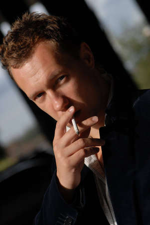 portrait of young man smoking a cigarette photo