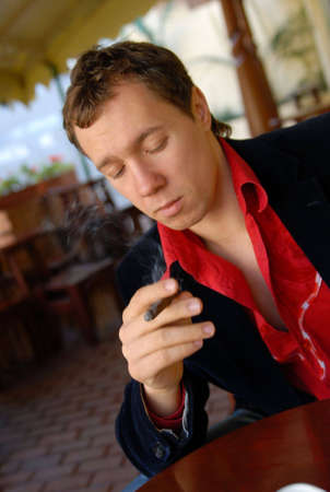 portrait of young man smoking a cigar