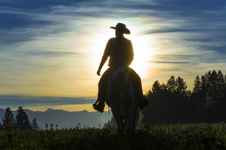 Cowboy riding across grassland with moutains behind, early moring, British Colombia, B.C., Canada 写真素材