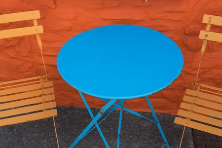 Blue round metal table set against orange wall & seats