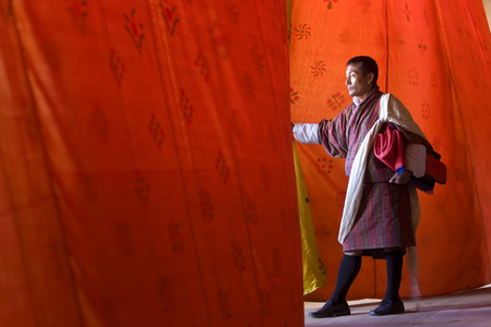 Thimpu, Bhutan - October, 2008: Man looking through curtains at performance, Festival, Trashichhoe Dzong (monastery), Thimpu, Bhutan