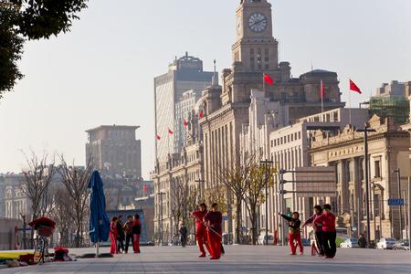 Shanghai, China - January, 2012: Early morning Tai Chi exercises with Customs House in the background, The Bund, Shanghai, China Editöryel