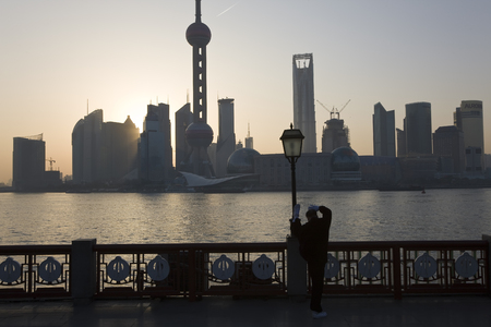 Shanghai, China - March, 2008: Man doing morning Tai Chi exercises on The Bund with a view to Pudong Shanghai, China