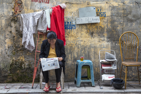 Hanoi, Vietnam - March, 2014: Woman reading newspaper on the street, Hanoi, Vietnam