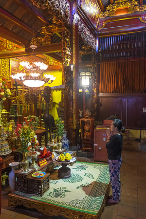 Hanoi, Vietnam - April, 2014: Woman praying at altar in Buddhist temple, Hanoi, Vietnam Editöryel
