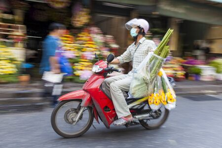 Bangkok, Thailand - February, 2013: Man on scooter with flowers, flower market, nr Chinatown,