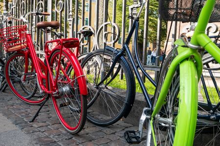 Colourful bicycles parked by railings in Copenhagen, Denmark