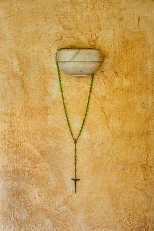 Religious cross with green beads hanging on a wall, near Pompei, Italy Banque d'images