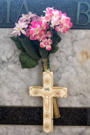 Cross and artifical flowers on a grave in Amalfi Cemetery, Amalfi Town, Salerno, Campania, Italy