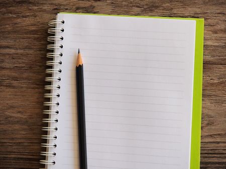 transcribe: Empty notebook paper for text with black pencil on wooden background Stock Photo